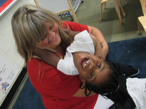 Staff photo by Cathy Spaulding<br /> Muskogee County Head Start teacher Melissa Whitmus gives Brooklyn Parker a playful hug during a break in classroom activities at Cherokee Elementary School.