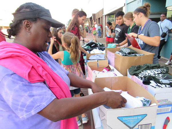 Staff photo by Cathy Spaulding<br /> Buyers look through T-shirts sold by the Muskogee High School Student Council during Muskogee Public Schools' Homecoming Festival Tuesday.