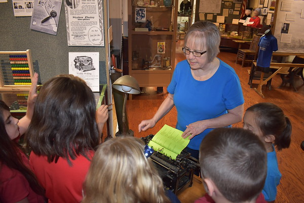 Staff photo by Mark Hughes<br /> Sue Tolbert, executive director of the Three Rivers Museum, explains to students how a manual typewriter operates. The students are from Helen Goosman's third-grade class at St. Joseph Catholic School. Tolbert retired after 10 years in her position.