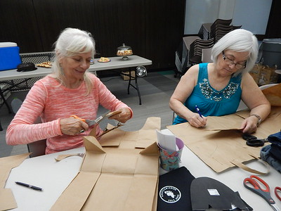 KENTON BROOKS/Muskogee Phoenix From left, Mary Preston, of Park Hill, and Debbie Thurber of Tahlequah, cut patterns out of paper. Those patterns will be used to cut blue jeans to make shoes for children and adults in Third World countries to prevent jiggers, a parasite that lives in or on the skin. The women were part of a shoe-cutting party in the Grant Foreman Room at the Muskogee Public Library on Thursday.