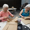 KENTON BROOKS/Muskogee Phoenix<br /> From left, Mary Preston, of Park Hill, and Debbie Thurber of Tahlequah, cut patterns out of paper. Those patterns will be used to cut blue jeans to make shoes for children and adults in Third World countries to prevent jiggers, a parasite that lives in or on the skin. The women were part of a shoe-cutting party in the Grant Foreman Room at the Muskogee Public<br /> Library on Thursday.
