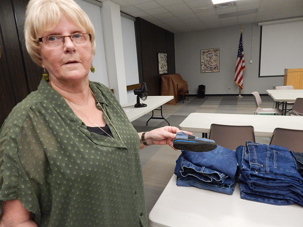 KENTON BROOKS/Muskogee Phoenix<br /> Muskogee's Becky Davis holds a finished shoe that was made from blue jeans used during the Shoe Cutting Party on Thursday in the Grant Foreman Room at the Muskogee Public Library.