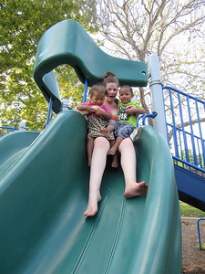 CATHY SPAULDING/Muskogee Phoenix Vanessa Campbell holds her children, Jeannessa Coleman, right, and J'Mario Coleman, as they venture down a twisty slide at Rotary Park.