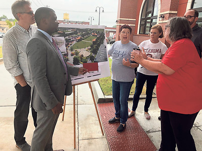 CHESLEY OXENDINE/Muskogee Phoenix (From left) City Manager Mike Miller, Senior Director of Public Affairs for Union Pacific Railroad's Brandon Morris, Indian Capital Technology Center Nursing instructor Wren Stratton, Muskogee Little Theatre Executive Director Coni Wetz, Three Rivers Museum Board of Directors Vice Chairman Roger Bell, and Neighbors Building Neighborhoods Executive Director Kim Lynch review an artist's rendering of a proposed green space in the Depot District. Morris presented the group with a $5,000 check from Union Pacific to help fund the project.