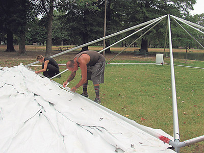 CATHY SPAULDING/Muskogee Phoenix Workers with Tents by A & J put the top on a tent being assembled Friday morning for a company's picnic at Honor Heights Park. According to Muskogee's AccuWeather webpage, occasional rain is expected Saturday with showers and thunderstorms expected Sunday.
