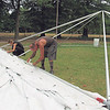 CATHY SPAULDING/Muskogee Phoenix<br /> Workers with Tents by A & J put the top on a tent being assembled Friday morning for a company's picnic at Honor Heights Park. According to Muskogee's AccuWeather webpage, occasional rain is expected Saturday with showers and thunderstorms expected Sunday.
