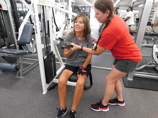 KENTON BROOKS/Muskogee Phoenix<br /> Shelly Sheffield of Gore, left, gets help from Strictly Fitness personal trainer Rachel Meinershagen with bicep curls during her twice-weekly workouts. Sheffield coordinates the Gore MS Walk, scheduled for Oct. 5 in the Gore Event Center.