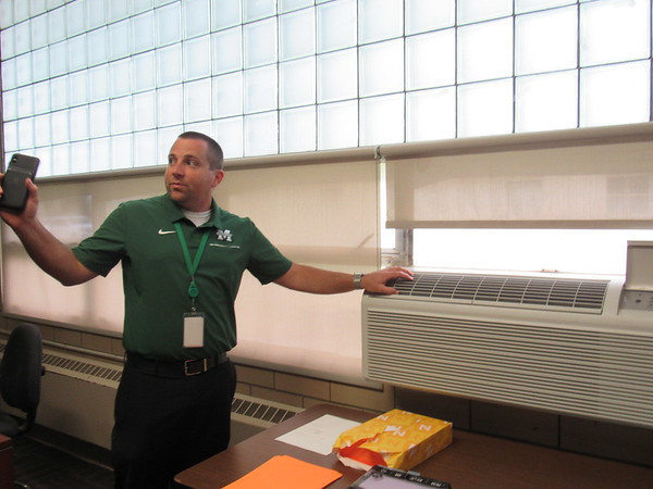 CATHY SPAULDING/Muskogee Phoenix<br /> Muskogee Public Schools Chief Information Office Eric Wells shows a window unit, an wall furnace and other outdated fixtures in a Tony Goetz Elementary classroom.