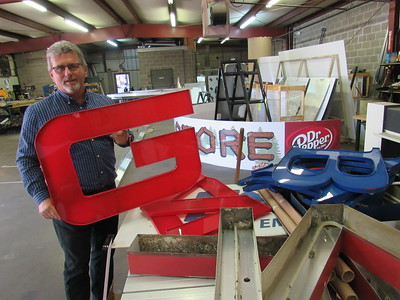 Staff photo by Cathy Spaulding Jack Stout holds a letter his sign company made for a local auto dealer. He said he enjoys all aspects of his business.