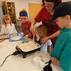 "KENTON BROOKS/ Muskogee Phoenix<br /> Library clerk Judy Walker, top, helps McKinley McCormick stir the mixture to make play dough as part of the STEAM program at Q.B. Boydstun Public<br /> Library in Fort Gibson this past week. From left, brother and sisters Baxley Reese, Rylee Reese and Ryder Reese watch and get ready to make their own batch of the ""gushy"" mounds of soft clay."