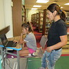 CATHY SPAULDING/Muskogee Phoenix<br /> Maria O'Callaghan watches her daughter, Rosie O'Callaghan, do homework on the 1960s at Muskogee Public Library. Gloomy skies and threats of rain Monday afternoon sent area youngsters into the library, where they found time to do their homework.