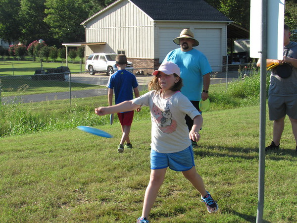 CATHY SPAULDING/Muskogee Phoenix<br /> Abby Murphy, 8, gets some disc throwing practice Tuesday afternoon at Civitan Park. Chase Murphy of Tahlequah said his family learned to play disc golf at the Civitan Park disc golf course.