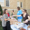 CATHY SPAULDING/Muskogee Phoenix<br /> First Baptist Church of Muskogee volunteer Julie McIntosh, right, hands a hot dog to Sadler Arts Academy student Faith Beech during Wednesday's See You After the Pole rally.