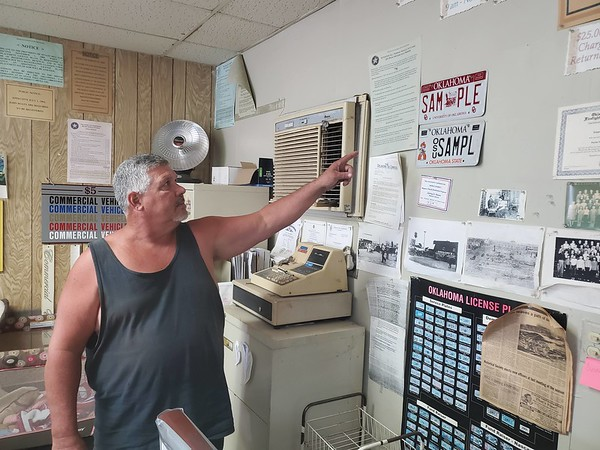 CHESLEY OXENDINE/Muskogee Phoenix<br /> Mike McCullough displays sample tags in what used to be his father Edgar Ray McCullough's tag agency in Porter. The agency was shut down in July following Edgar Ray's death in May.