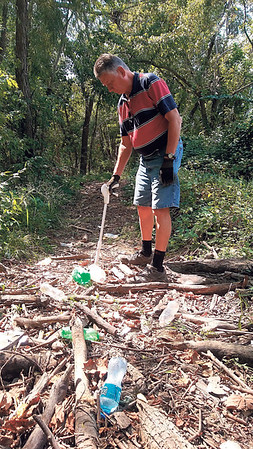 Staff photo by Wendy Burton<br /> Larry Hoffman picks up garbage left after flooding along the Port of Muskogee running trail during a recent visit. Hoffman said volunteers are needed at 8 a.m. Saturday to help clean up thousands of pieces of plastic and trash along the popular running trail.