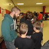 CATHY SPAULDING/Muskogee Phoenix<br /> Wednesday morning showers sent students, teachers and parents inside Hilldale High School for the annual See You at the Pole prayer gathering, held before school. Southeast Baptist Church youth pastor Shane Haff, left, leads a prayer while Kim Dubin and her children gather in a circle during a See You at the Pole prayer service before school Wednesday at Hilldale High School. Dubin's children are, from second left, Gavin Dubin, Garrett Dubin and Kensly Dubin. See You at the Pole is an annual international day of student-led prayer services.