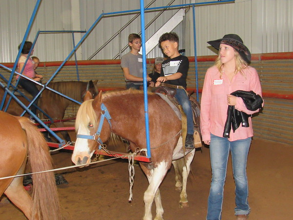 Staff photo by Cathy Spaulding<br /> Connors State College rodeo team member Hannah Jackson  accompanies Oklahoma School for the Blind first-grader Braylen Fuller for a pony ride Wednesday at Silver Spur Western Lodge. OSB students spent their 13th annual Western Heritage Day at the lodge.