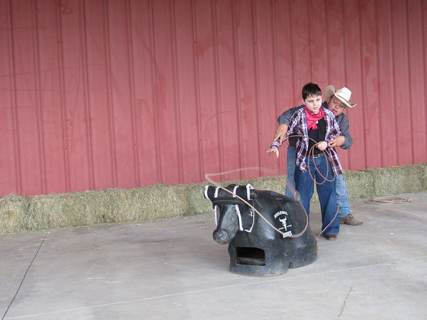 CATHY SPAULDING/Muskogee Phoenix<br /> Oklahoma School for the Blind fifth-grader Dayton Baccus swings a lasso while Connors State College student Chase Wolf guides him. The two practiced roping Wednesday during Western Heritage Day.