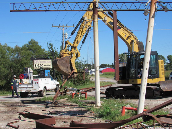 CATHY SPAULDING/Muskogee Phoenix<br /> An excavator operator lifts debris from a gas pump canopy that had been demolished earlier Thursday morning. The old gas station is located near the 3400 block of North 32nd Street.