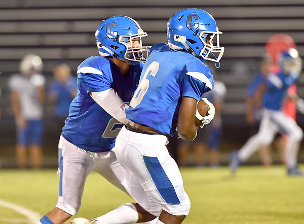 JIM WEBER/Phoenix Correspondent<br /> Jacob Barrett hands off to Dontairre Fisher for a long gain during the Wildcats 63-6 win over Tulsa Webster on Friday.