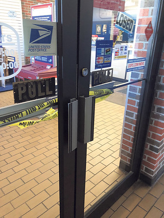 "CHESLEY OXENDINE/Muskogee Phoenix<br /> The area leading to the front counters at the U.S. Post Office in Fort Gibson is taped off Friday by police after a ruptured package caused a ""minor explosion"" inside the facility."