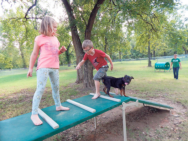 KENTON BROOKS/Muskogee Phoenix<br /> Madelyn Diamond, 9, and her brother Hunter, 7, play with their new dog Friday at the Coody Creek Bark Park at South Second Street in Muskogee. The children's mother, Laura, pictured in the background, said they adopted the 5-month-old dog, which they named Rose, on Thursday and took him out to exercise while running around the park's Small Dog Area. The Diamonds said they have two other dogs.