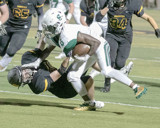 SHANE KEETER/Special to the Phoenix<br /> Muskogee's Jimmie Coleman stiff arms a Sand Springs defender trying to avoid being pulled to the ground during Friday's game in Sand Springs. Coleman recorded five touchdowns at the Roughers beat the Sandites 45-27.