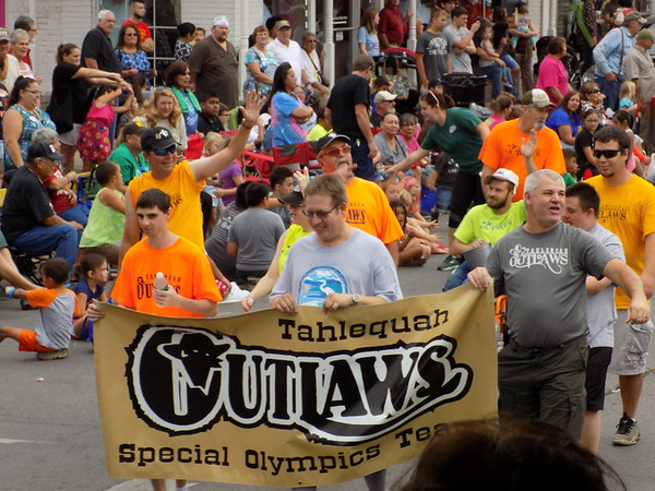 Staff photo by Mike Elswick<br /> Members of the Cherokee County Outlaws Special Olympics teams wave to the crowd during Saturday's 65th annual Cherokee National Holiday Parade.
