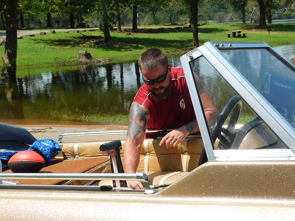 KENTON BROOKS/Muskogee Phoenix<br /> Andrew Jobe of Broken Arrow checks on his boat as he loads it up after fishing and enjoying the day with his son Abel and wife Tanya at Lake Fort Gibson at Sequoyah State Park. Jobe set up at the place his father brought him to camp and fish when he was younger.
