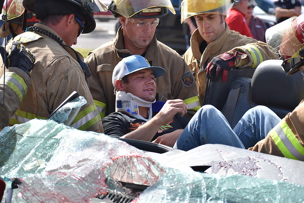 Staff photo by Mark Hughes<br /> Ty Brison, wearing a neck brace, is on a backboard being removed from a vehicle in a mock accident Friday morning next to the Civic Center.