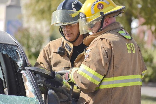 """Staff photo by Mark Hughes<br /> Firefighters from Station One use the Jaws of Life to remove the truck's roof to """"rescue"""" a passenger during Friday's mock training event at the Civic Center. """"Getting to use our Jaws of Life, our pneumatic air bags and our struts helps fine tune training we've already received,"""" said Acting Assistant Chief Kevin Warlick."""