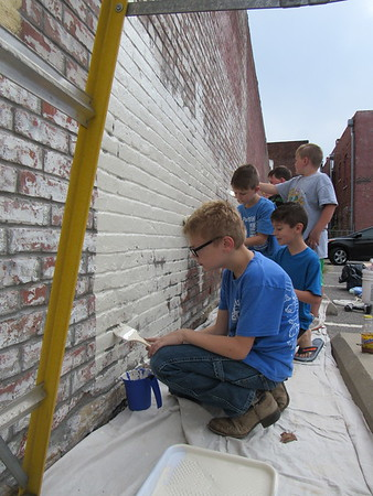 CATHY SPAULDING/Muskogee Phoenix<br /> Members of Cub Scout Pack 622 spent Saturday morning painting the side of a pawn shop north of Okmulgee Avenue on Main Street. Paint was donated by Keep Oklahoma Beautiful. It was the pack's community service project. Cub Scouts, from left, Braxton Garner, Wyatt Fletcher, Aidan Brown, Hunter Ward and Mason Miller line up along a brick wall to paint it.