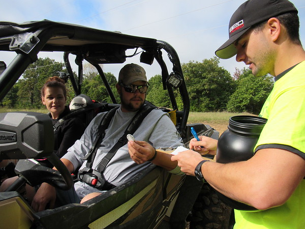 CATHY SPAULDING/Muskogee Phoenix<br /> Kristen Barnett and Dustin Blackman stop their four-wheeler to get a pick a poker chip from Cheston Vaughn during Saturday's Poker Run at Gruber ORV Park. Nearly 500 people drove their Jeeps, four-wheelers, motorcycles and other off-road vehicles through Gruber ORV Park on Saturday for the park's second annual Poker Run. Participants visited five stops along a route to select numbered poker chips. Half of the proceeds went to participants with the top five hands. The other half went to upgrade the park.