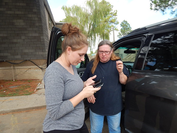 CATHY SPAULDING/Muskogee Phoenix<br /> Deanna Baty, left, and her mother, Linda Hall, scan their smartphones for pictures of Hall's daughter, Kevyawna Roshea Jackson Hall, who was killed in a shooting Friday night in an apartment on South York Street.