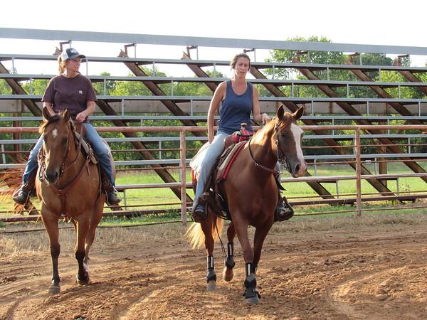 CATHY SPAULDING/Muskogee Phoenix<br /> Ronda Hix, left, and Sarah Hix-Tannehill, both of Tahlequah, ride their horses around the Fort Gibson Roundup Club arena before a barrel-racing practice session Thursday. It was their first visit to the arena.