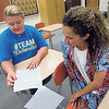 Staff photo by Cathy Spaulding<br /> Fort Gibson Middle School math teacher Kim Morgan, left, goes over a mentoring checklist with tech engineering teacher Yanin Maharaj, a first-year teacher. Morgan has been a mentor to several new teachers in her 10 years at Fort Gibson.