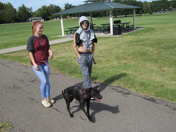 CATHY SPAULDING/Muskogee Phoenix<br /> Madison Fulton and Buddy Lewis took advantage of a break in Tuesday's rain showers to walk Maxxine around Robison Park.