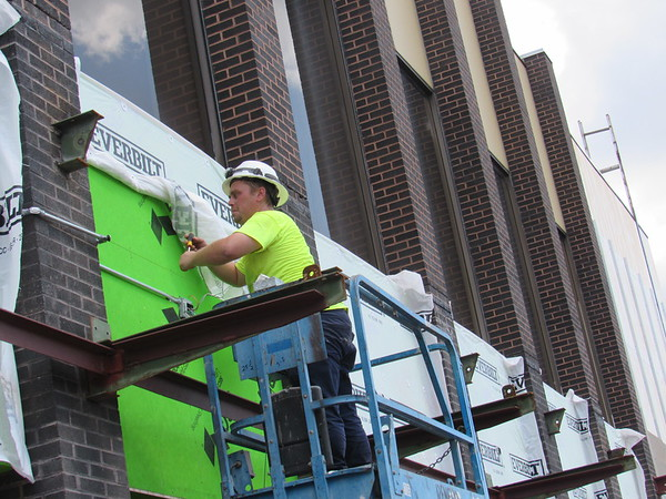 CATHY SPAULDING/Muskogee Phoenix<br /> An electrician with Renfro Electric installs a covered electric line across the exterior of Muskogee Public School's central administration offices Wednesday afternoon.
