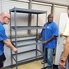 CHESLEY OXENDINE/Muskogee Phoenix<br /> (from left to right) Rotary Club President Blake Farris joins Arthur Furgerson in installing a shelf at the Muskogee Community Food Pantry, while pantry coordinator Tom Carment looks on.