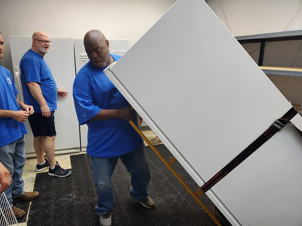 Rotary Club President Blake Farris looks on as volunteer Arthur Furgerson moves a refrigerator from one end of the Muskogee Community Food Pantry to another during Friday's Lake Area United Way Day of Caring event.