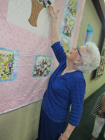 Staff photo by Cathy Spaulding<br /> Faye Dean Boydstun shows details of one of her quilts hanging in the Keefeton Trinity Baptist Church sanctuary. Her quilts hang as part of the church's 47th annual Ole Timer's Day. The event will be Sunday  following the 10:50 a.m. service.