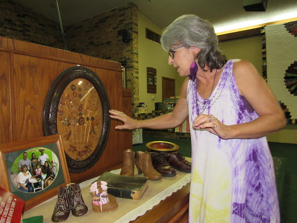 Staff photo by Cathy Spaulding<br /> Keefeton Trinity Baptist Church member Susan Lewis shows an artwork and shoe display the church set up for its 47th annual Ole Timers Day. She said her grandmother made the artwork out of weeds and seeds.