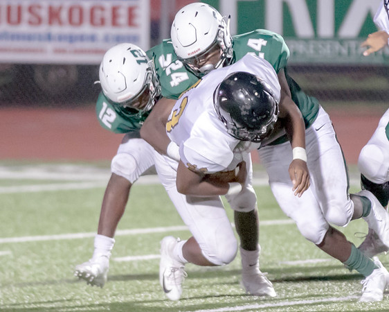 SHANE KEETER/Special to the Phoenix<br /> Muskogee's Caleb Webb, left, and Colton Edwards tackle Midwest City's Kristawan Friday in the Roughers' 16-14 loss on Friday.