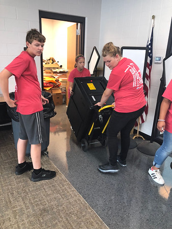 CHESLEY OXENDINE/Muskogee Phoenix<br /> From left: Eighth-grader Peyton Capps guides fellow eighth-grader JaiCee Luster and senior Megan Ballard (right) in rolling a large container out of a closet at the Dr. Martin Luther King Jr. Community Center. The students were part of a volunteer group helping during the Lake Area United Way Day of Caring.