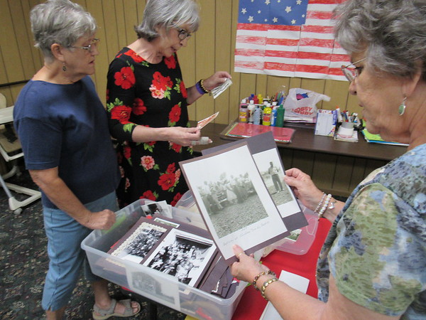CATHY SPAULDING/Muskogee Phoenix<br /> Keefeton Trinity Baptist members, from left, Betty Fields Buford, Susan Lewis and Judy Croftcheck, sort through old photos to be displayed during the church's Old Timers Day.