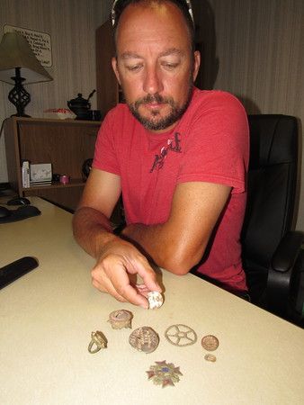 """CATHY SPAULDING/Muskogee Phoenix<br /> Aaron Dunlap shows a small sampling of """"relics"""" he found while metal detecting. He likes researching the items to learn their stories."""