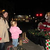 CATHY SPAULDING/Muskogee Phoenix<br /> Erin Climer watches her daughter, Georgia Pinkstaff, 3, greet Santa from a safe distance Monday at Fort Gibson's Christmas Tree Lighting.