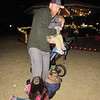 CATHY SPAULDING/Muskogee Phoenix Dustin Nettle of Fort Gibson, tries to hold his 1 1/2-year-old son Dylan Nettle, while trying to walk in a pair of living shoes — Sadie Baucher, left, and Kristyn Nettle, both 4. The family visited the Fort Gibson Christmas Tree Lighting on Monday evening.