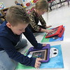 CATHY SPAULDING/Muskogee Phoenix<br /> First-graders Luke Cantrell, left, and Kimber Nail crop and edit photos they took with their tablet computers. Fort Gibson elementary art teacher Lauran Buckmaster is getting four more computers.