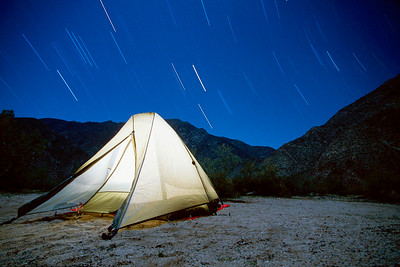 Lit tent with star trails in Anza Borrego Desert State Park, CA. USA
